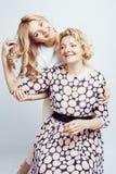 Madre con la hija junta que plantea la sonrisa feliz en el fondo blanco con el copyspace, concepto de la gente de la forma de vid Fotos de archivo