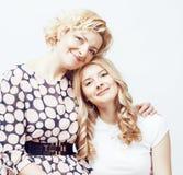Madre con la hija junta que plantea la sonrisa feliz aislada en el fondo blanco con el copyspace, concepto de la gente de la form Imágenes de archivo libres de regalías
