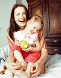 Madre con la hija junto en cama que sonríe, cierre feliz de la familia para arriba, concepto de la gente de la forma de vida, fam Imagen de archivo libre de regalías