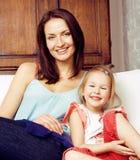 Madre con la hija junto en cama que sonríe, cierre feliz de la familia para arriba, concepto de la gente de la forma de vida, fam Imagen de archivo