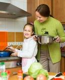 Madre con la hija que cocina en la cocina Fotografía de archivo