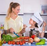 Madre con la hija que cocina los veggies Foto de archivo libre de regalías