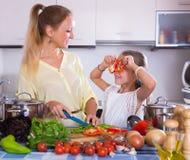 Madre con la hija que cocina los veggies Imagen de archivo libre de regalías