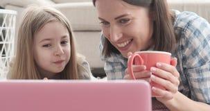 Madre con la hija que desayuna y que mira película almacen de metraje de vídeo
