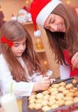Madre con la hija que hace las galletas de la Navidad Fotos de archivo libres de regalías