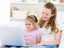 Madre con la hija que mira la computadora portátil Imagen de archivo