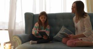 Madre con la hija que se sienta en el sofá usando la familia joven sonriente feliz de la tableta metrajes