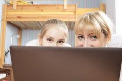 Madre con la hija que sonríe detrás del ordenador portátil Fotografía de archivo