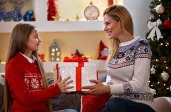 Madre con la hija que sostiene la caja con el regalo de la Navidad foto de archivo