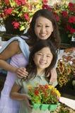 Madre con la hija que sostiene las flores jovenes en retrato del cuarto de niños de la planta Imagen de archivo libre de regalías