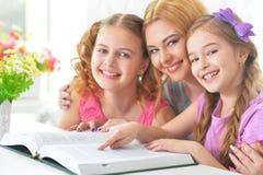 Madre con la lectura de las hijas imagen de archivo