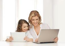 Madre con la muchacha que mira a la PC del ordenador portátil y de la tableta Imagen de archivo libre de regalías