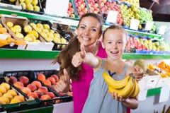 Madre con la muchacha que muestra los pulgares para arriba en supermercado Imágenes de archivo libres de regalías