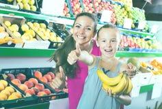Madre con la muchacha que muestra los pulgares para arriba en supermercado Fotos de archivo libres de regalías