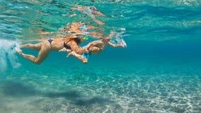 Madre con la nadada del niño subacuática con la diversión en el mar Imágenes de archivo libres de regalías