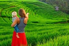 Madre con la passeggiata del bambino sul terrazzo verde del riso bali Fotografia Stock