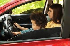 Madre con la pequeña hija linda que conduce el coche NI?O EN PELIGRO imagenes de archivo