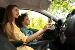 Madre con la pequeña hija que conduce el coche junto NI?O EN PELIGRO fotografía de archivo