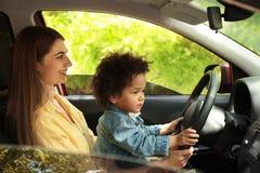 Madre con la pequeña hija que conduce el coche junto NI?O EN PELIGRO foto de archivo