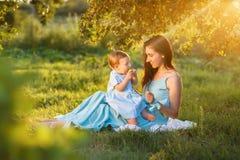 Madre con la pequeña hija que juega en hierba verde imagen de archivo libre de regalías