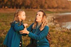 Madre con la pequeña hija que sopla al diente de león en naturaleza al aire libre Concepto feliz de la familia, de la niñez y  foto de archivo libre de regalías