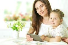 Madre con la pequeña hija que usa la tableta Foto de archivo libre de regalías