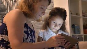 Madre con la pequeña hija que usa la tableta y sentándose en el sofá en el hogar moderno, concepto de familia con el artilugio, d almacen de metraje de vídeo