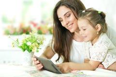 Madre con la piccola figlia che per mezzo della compressa Immagini Stock