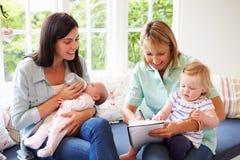 Madre con la reunión del bebé con el visitante de la salud en casa Imagen de archivo libre de regalías