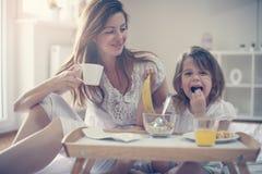 Madre con la sua piccola figlia che mangia prima colazione nel letto Immagini Stock Libere da Diritti