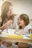 Madre con la sua piccola figlia che mangia prima colazione nel letto Fotografie Stock