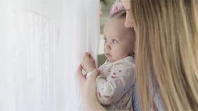 Madre con la sua piccola neonata che sta vicino alla finestra e che guarda fuori archivi video