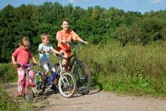 Madre con las bicis del paseo de los niños fuera de la ciudad Foto de archivo libre de regalías