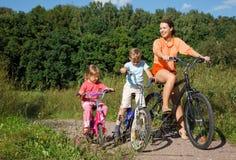 Madre con las bicis del paseo de los niños fuera de la ciudad Imágenes de archivo libres de regalías