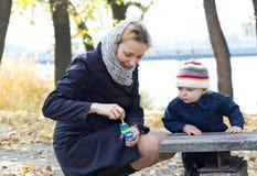Madre con las burbujas que soplan del pequeño hijo Fotografía de archivo