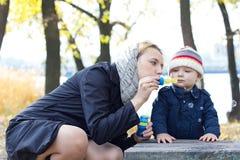 Madre con las burbujas que soplan del pequeño hijo Imágenes de archivo libres de regalías