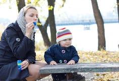 Madre con las burbujas que soplan del pequeño hijo Imagen de archivo