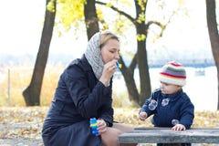 Madre con las burbujas que soplan del pequeño hijo Foto de archivo