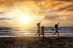 Madre con las hijas en la playa durante sus vacaciones de familia imágenes de archivo libres de regalías