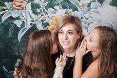Madre con las hijas que comparten un secreto Imágenes de archivo libres de regalías