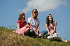 Madre con las hijas que se sientan en el banco de la hierba Imagen de archivo libre de regalías