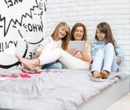 Madre con las hijas que usan la tableta digital en dormitorio Imagen de archivo