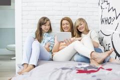 Madre con las hijas que usan la tableta en dormitorio Fotos de archivo