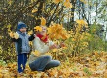 Madre con las hojas de arce que lanzan del muchacho Foto de archivo