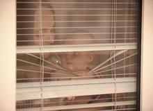 Madre con lo sguardo del figlio del bambino attraverso i ciechi fotografia stock