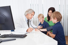 Madre con los cabritos en la oficina de los doctores Fotos de archivo libres de regalías