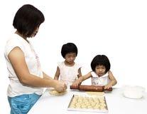 Madre con los cabritos que aprenden haciendo buiscuits Imágenes de archivo libres de regalías