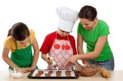 Madre con los cabritos que preparan las tortas Imagen de archivo libre de regalías