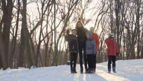 Madre con los hijos que agitan las manos a la cámara en parque del invierno almacen de metraje de vídeo