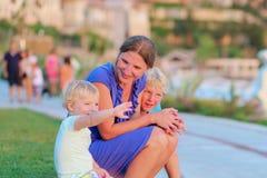 Madre con los niños al aire libre en la puesta del sol Imágenes de archivo libres de regalías